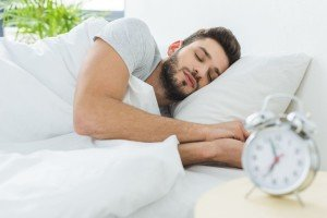 handsome bearded man sleeping in bed in the morning, alarm clock on foreground