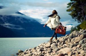 girl_walking_along_waterline_with_big_bag